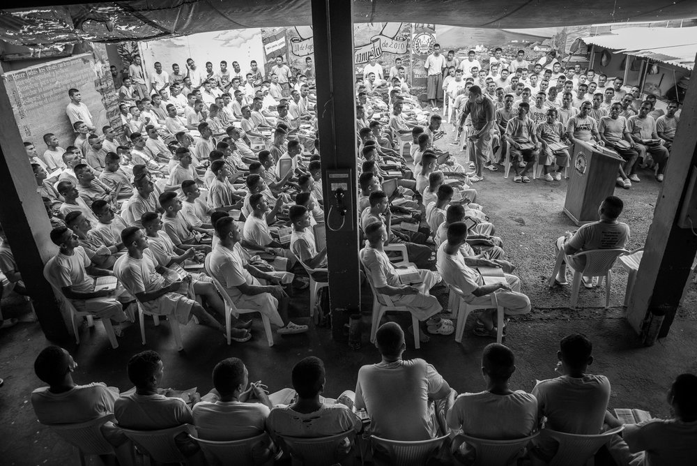 """The yards 4, 5 and 6 of the jail, the inmates are gathered to listen the pastor of the Final Trumpet church. According to the prison director, half of the prisoners are serving a sentence of more than 30 years (and a quarter more than 50 years). If gang affiliation is lifelong, there is an exception: when """"God reclaims a soul"""", of course with death but also for devotion to religious activities. Conversion became the only way tolerated by the gang leaders to get out alive. With Christianity, the prisoners find a bit of inner peace given by the hope of reward for their repentance and good behaviors."""