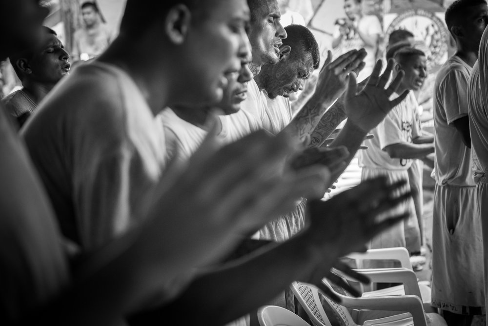 Prisoners of the yards 4, 5 and 6 of La Gotera jail participe to the worship of the Final Trumpet church. They are singing a christian song glorifying God amidst drumming and electric guitars melodies played by the inmates.