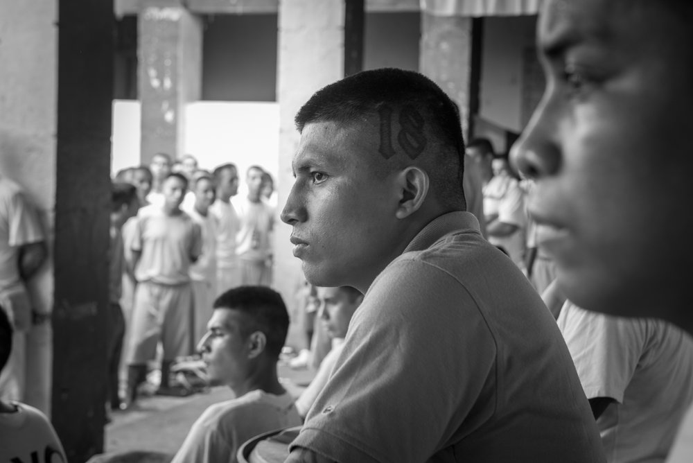 """Inmates at the 1, 2, and 3 yards are participating to the worship of """"Strong Tower"""" church in La Gotera jail. At the center, one of the inmates has a 18 tattoo on the skull in reference to his former gang, 18th Street."""