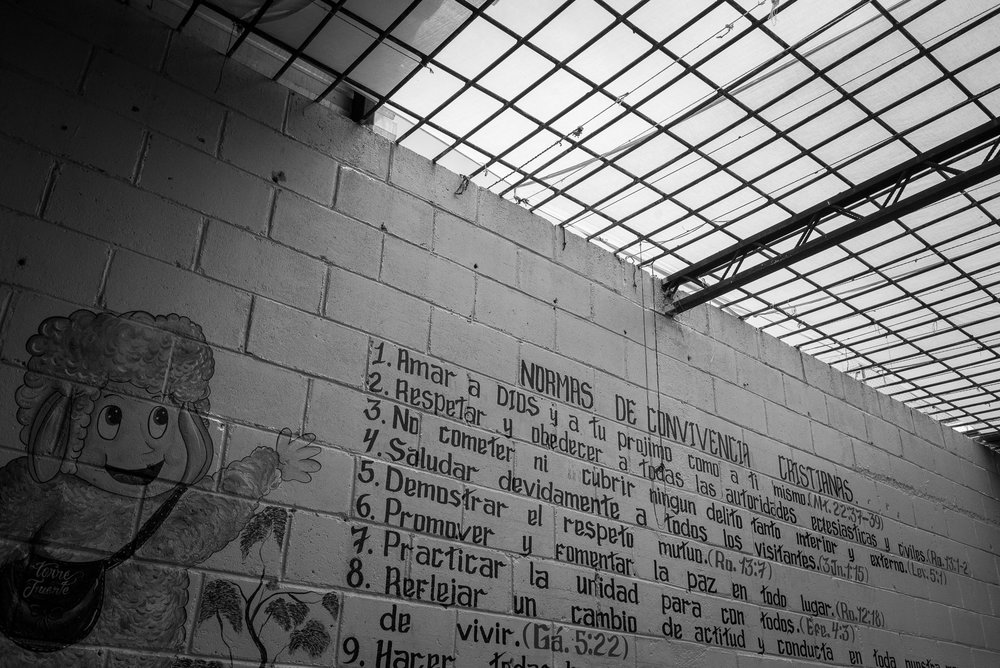 "On a wall of the jail, a wall painting itemizes the rules the converted prisoners have to follow. Between them, the second says: ""Respect and obey to the ecclesiastic and civil authorities"". At the left side, a ewe painted represents a prisoner in reference to the traditional representation in the evangelical symbolism of a herd that have to follow the recommendation of the pastor."