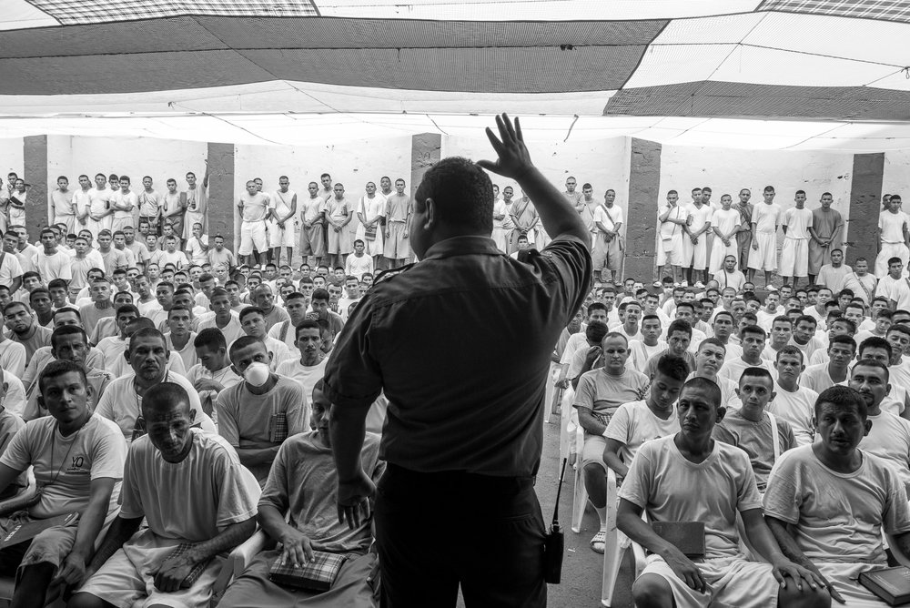 Oscar Benavides, director of La Gotera jail, gives a speech to the prisoners. In two short years, the jail has tipped to Evangelical Protestantism with 1,500 prisoners sentenced for their activities in the 18th Street, now converted. In charge since three years, the jail director made the bet to give more power to some incarcerated pastors and former gang members. From a first yard, the conversion extended progressively to the five others. Only some seventy diehards, isolated from the others, still refuse to convert.