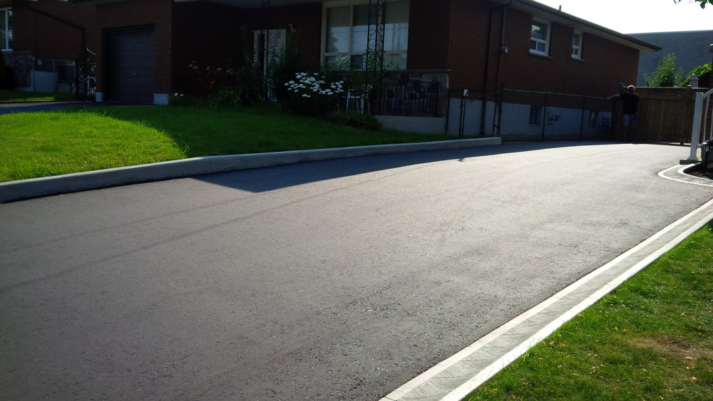 Asphalt drive way with concrete curbing.