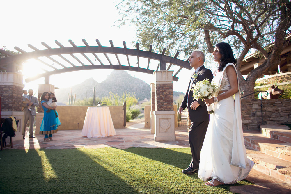 Father walks bride down the aisle with mountain in background