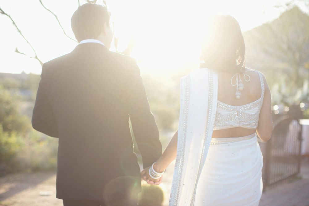 Bride and groom holding hands during wedding at Sassi with sun flare