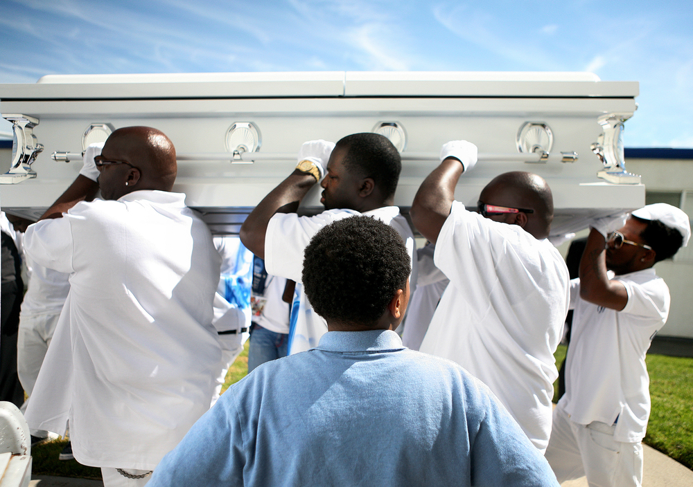 Pallbearers carry the coffin of Davon Ellis, a 14-year-old boy who was killed by gunfire while walking to a store in Oakland, California.
