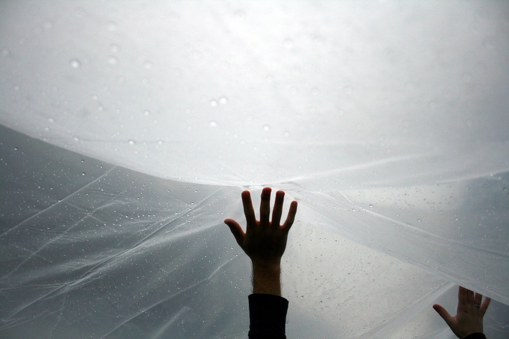 A UC Berkeley student protester holds a tarp up to protect against the rain at a protest of tuition increases that drew thousands despite the rainy weather.