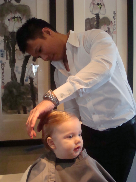 Well this is my youngest daughter Anna Grace, at the time 8 months, getting a haircut with Ringo at the Mandarin Oriental Hotel Salon in Hong Kong.  Both Anna Grace, 3 years old now, and her sister Mary, 10 months,  got their first haircut by my mom while they were sleeping.  My girls were born with more than a full head of hair.  They seriously needed a hair clip from birth.  I hate having their hair cut.  I know it grows back but nonetheless, I don't like doing it.  A few nights ago I caught a glimpse of my beautiful 3 year old running around the house and an image popped in my head of Ruby Sue, Clark Griswald's niece in Christmas Vacation.  If you haven't seen this, your Christmas hasn't been complete.  I'm pretty sure Ruby Sue never had a haircut or a hairbrush for that matter.  After dinner I cut 5 inches!!!  It would have been less if it weren't for my husband in the background taunting me to really go for it.  Well we gave her sparkling apple juice, a bowl of marshmallows and a plastic garbage bag for her drape.  Since the haircut I've bought some proper scissors but I had to use a very heavy pair of dressmaker shears.  Its done; just don't look too carefully.