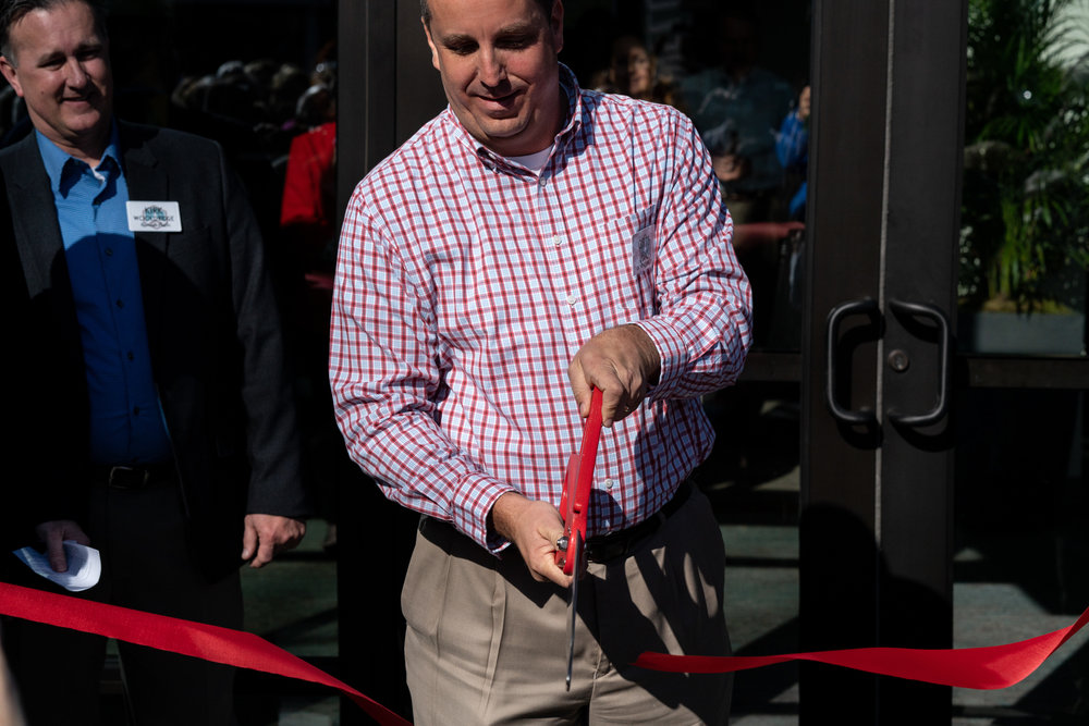 Construction Management Team Chairman Curtis Janis officially cuts the ribbon opening our remodeled space.