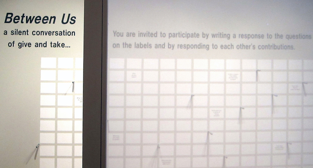 A wall text invited viewers to respond to 11 open-ended questions that were printed and distributed throughout a grid of blank labels. Participants could stand at the wall to write on one of the blank labels surrounding the questions. Writing pens were mounted in metal sleeves placed in the wall surface. A custom bench designed with slots for notebooks and pens provided an alternative seat for response or reflection.