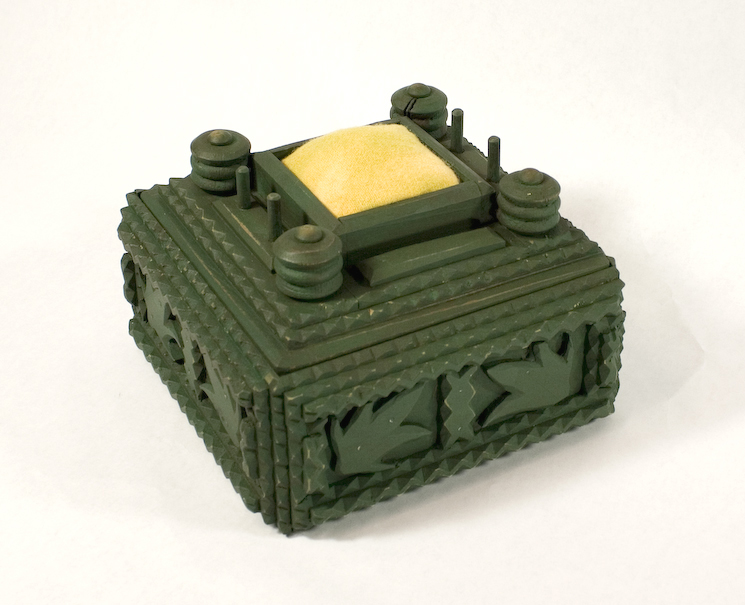 Green tramp art sewing box with yellow pin cushion.