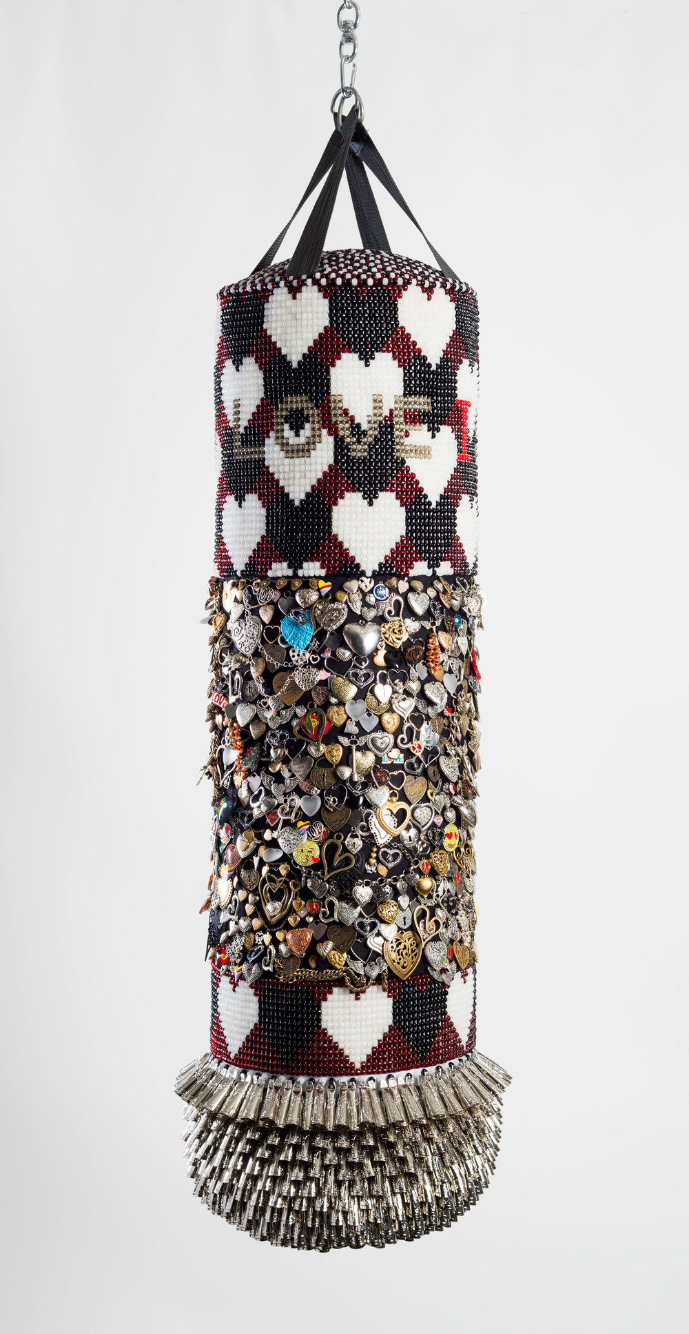 "Jeffrey Gibson. ""LOVE IS THE DRUG"" (2017). Repurposed vinyl punching bag, glass beads, found and collected mixed metal charms, cotton, artificial sinew, tin jingles, acrylic felt. 55 x 13 INCHES."