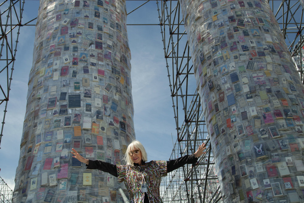 "Marta Minujín poses in front of ""The Parthenon of Books"""