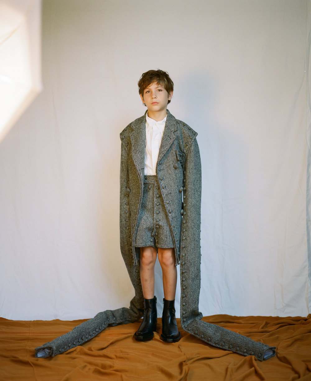 Jacob Tremblay | THOM BROWNE coat, shirt, and shorts and VETEMENTS shoes available at Mona Moore.