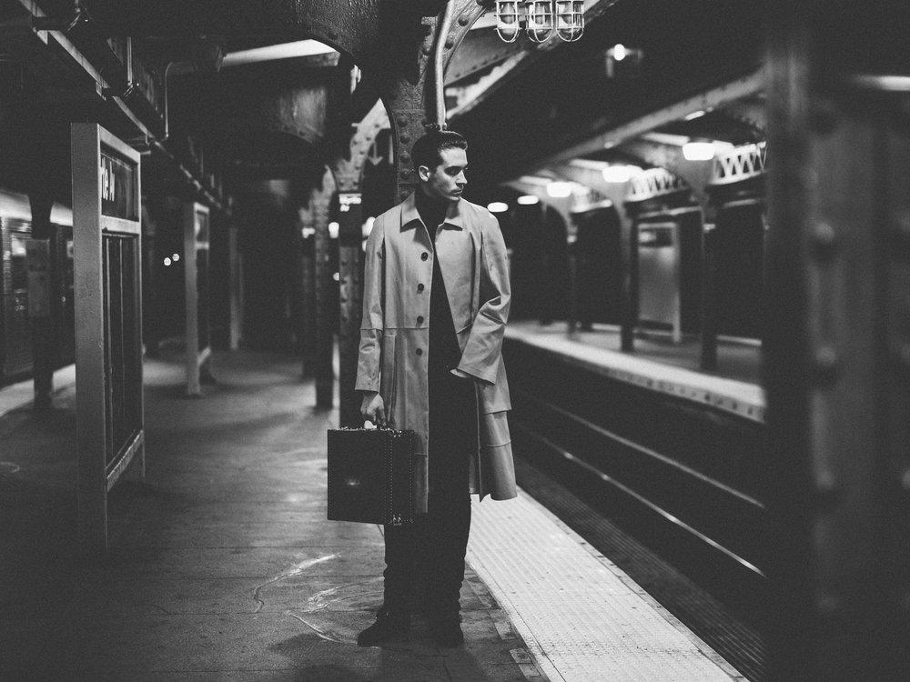 JIL SANDER  coat,  HUGO BOSS  turtleneck,  GUESS  pants,  SAINT LAURENT BY ANTHONY VACCARELLO  shoes, and  LOUIS VUITTON  suitcase.