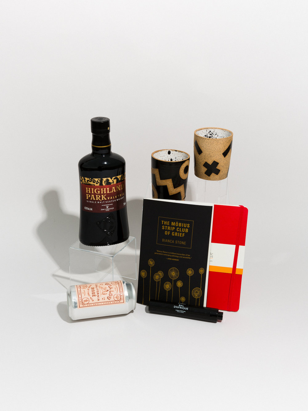 HIGHLAND PARK  Valkyrie scotch whiskey,  RECREATION CENTER  ceramic tumblers,  THE MÖBIUS STRIP CLUB OF GRIEF  book of poems,  MOLESKINE  notebook,  BYREDO  kabuki perfume, and  UNA LOU ROSÉ  wine.