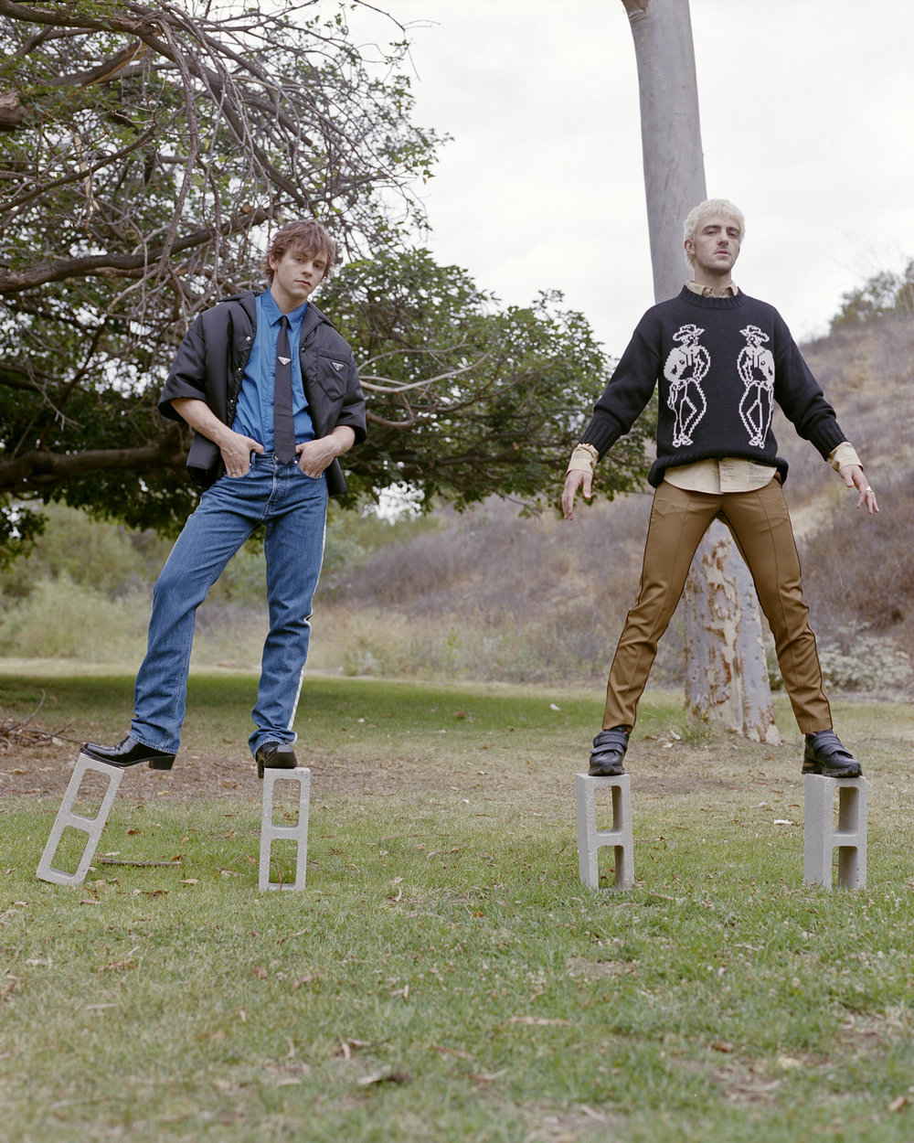 Left to right: Ross wears  PRADA  jacket, shirt, and tie and  CALVIN KLEIN JEANS  jeans and boots. Rocky wears  OVADIA & SONS  sweater and pants,  LINDER  shirt, and  ERMENEGILDO ZEGNA COUTURE  shoes.