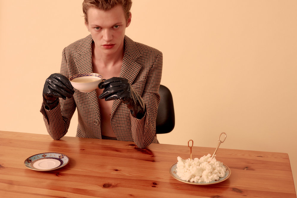 """Turner  wears   RAF SIMONS     blazer and gloves and his own jewelry.   ATE VAN APELDOORN     Simple Pine Table available at Amsterdam Modern,   BERNARDAUD     """"Grace"""" cream soup cup, saucer, and plate, and   HERMÈS     """"Grand Attelage"""" gold plated spoon and knife."""