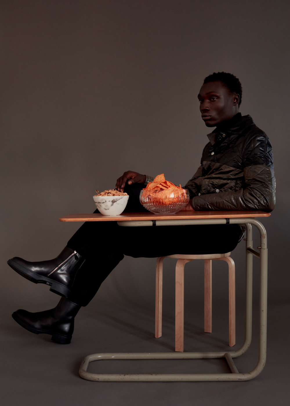 """Yoeli  wears   HERMÈS     jacket, pants, and shoes.   AMSTERDAM MODERN     """"Breakfast in Bed"""" table available at Amsterdam Modern,   WATERFORD     """"Lismore"""" diamond encore bowl, and   PROUNA     marble cereal bowl."""