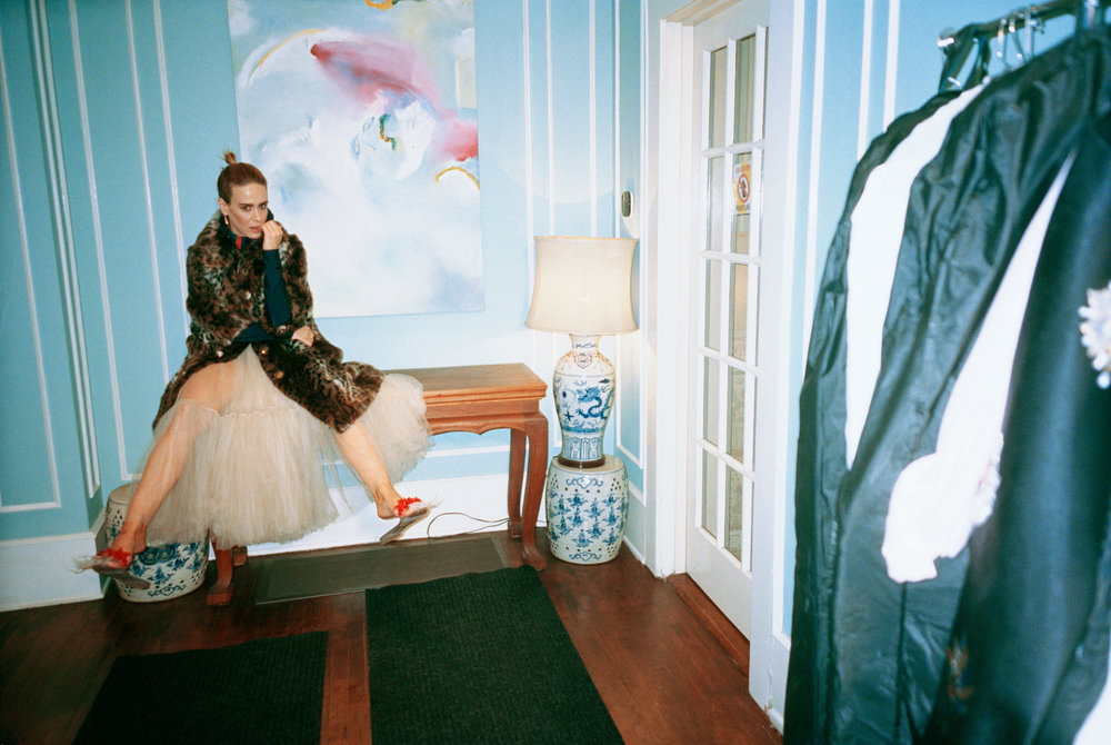 ERDEM     coat,   PACO RABANNE     bodysuit,   DIOR     skirt,   SIMONE ROCHA     shoes, and   LAGOS     earrings.