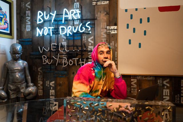 "Marcel Katz with Schoony ""Bruiser Panel"" statue, CB Hoyo ""Buy Art, Not Drugs"" neon light fixture, Bertrand Fournier ""The Birth of the Rainbow"" painting, Detroitwick ""Shreds XXL"" sculpture"