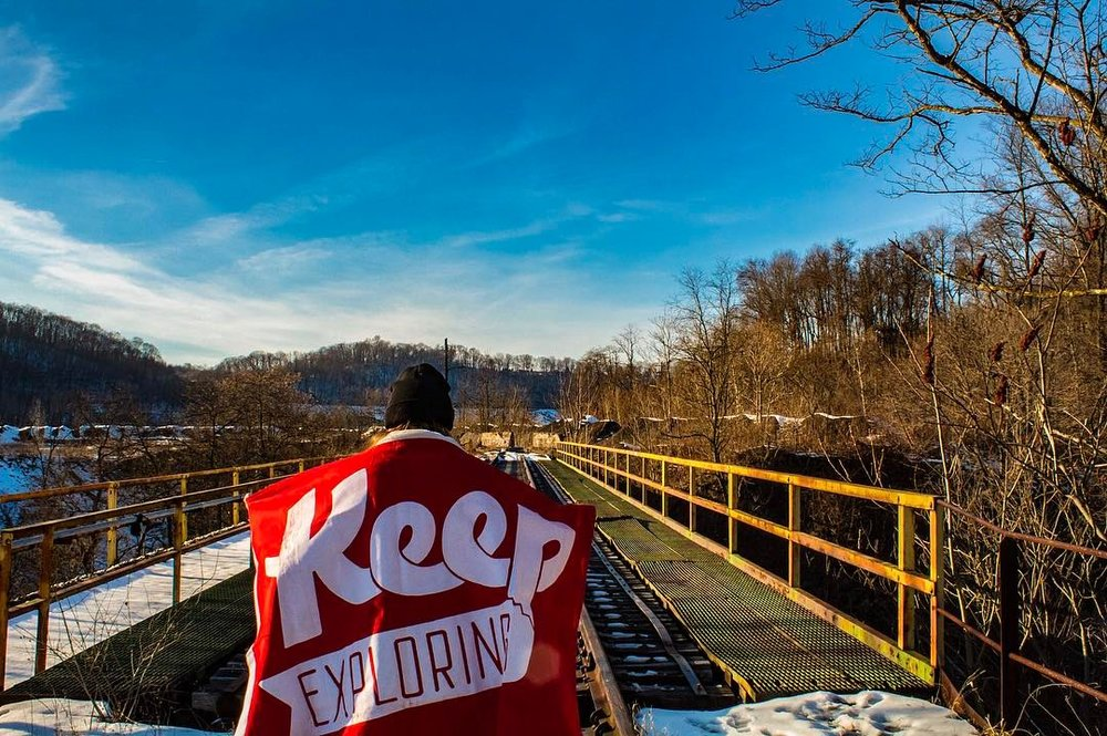 @adrimariemedia posed with our iconic flag before adventuring on some abandoned tracks