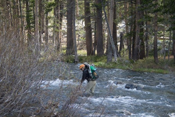 Stream crossing with ultralight pack, orange hat and re-purposed stick as assistance device.