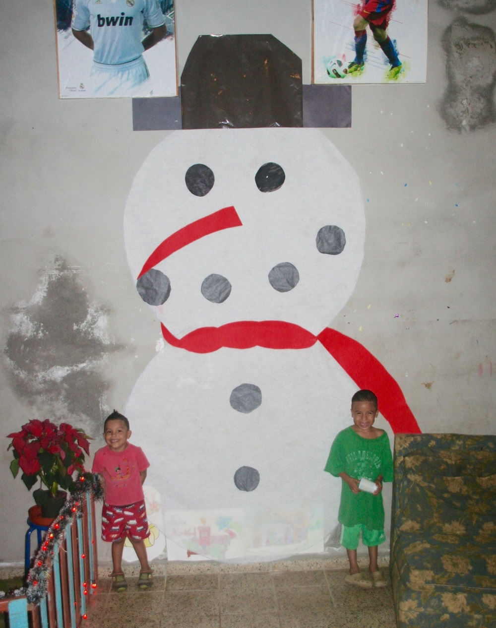 Edwin and friend posing in front of a giant snowman they helped make on the wall of their dorm during Christmas.