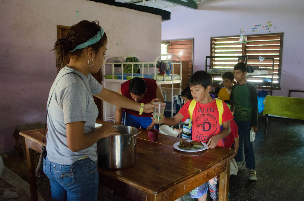 Madrina Carolina passing out tamales and café con leche to her boys in Hogar 6 last Christmas.