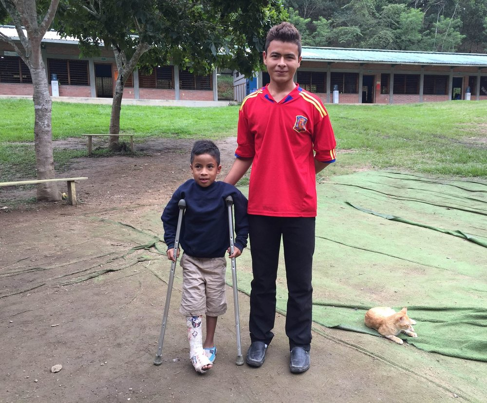 Dominic assisting one of our younger students at the Amigos school during his vacations from  colegio  (high school)