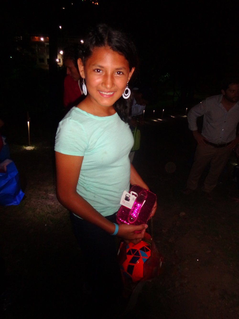 Maria receiving presents donated by her padrinos from the U.S. on Christmas last year