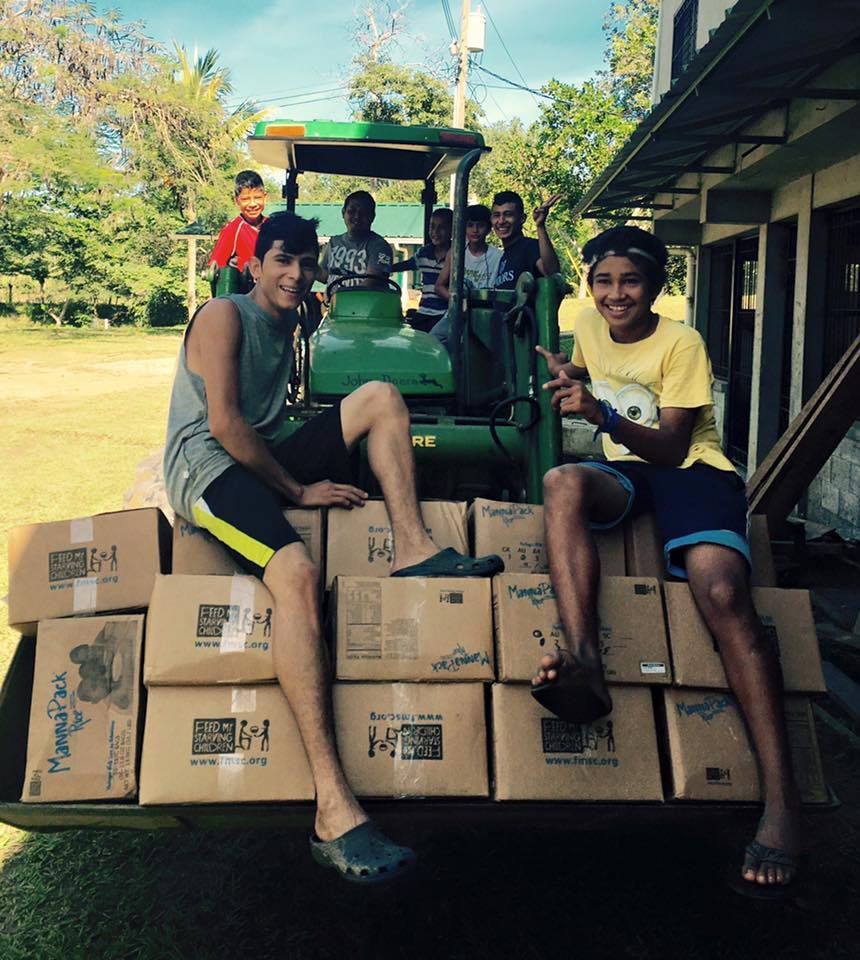 Adán (right) and friends helping move donations wth the tractor