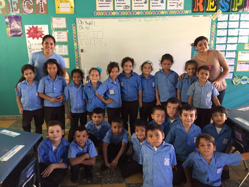 Profe Evelyn, pictured on the left, with her 2nd grade class.