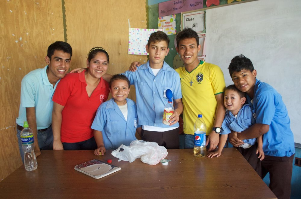 Profe Evelyn, pictured in the red shirt on the left, with EducaTodos students and teachers at the science fair in 2016.