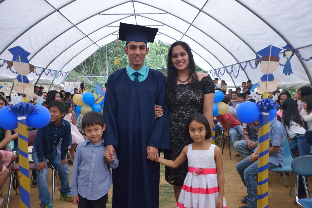 Here, Profe Evelyn, along with two first grade students, escort Profe Miguel, fellow teacher and a close friend of Profe Evelyn's, down the aisle during the December graduation ceremony at our school. Profe Miguel earned his associates degree in education.