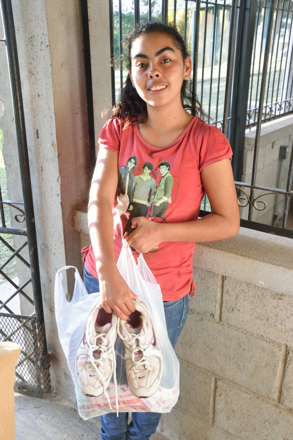 One of our teenage girls walks away with a bag of new clothes and even tennis shoes for gym class.