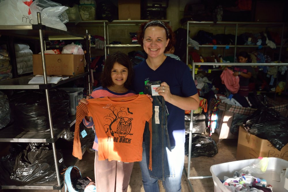 Genevieve, who helps organize, manage, and run 'tienda' showing off new clothes with one of our young girls.