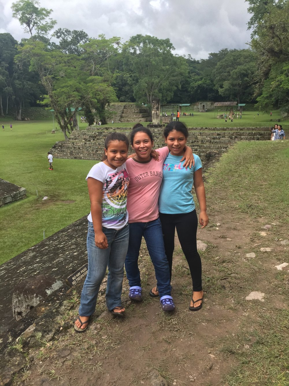 Elisa, pictured on the right, with her older sister and a friend visiting the Mayan Ruins in Copan Ruinas.
