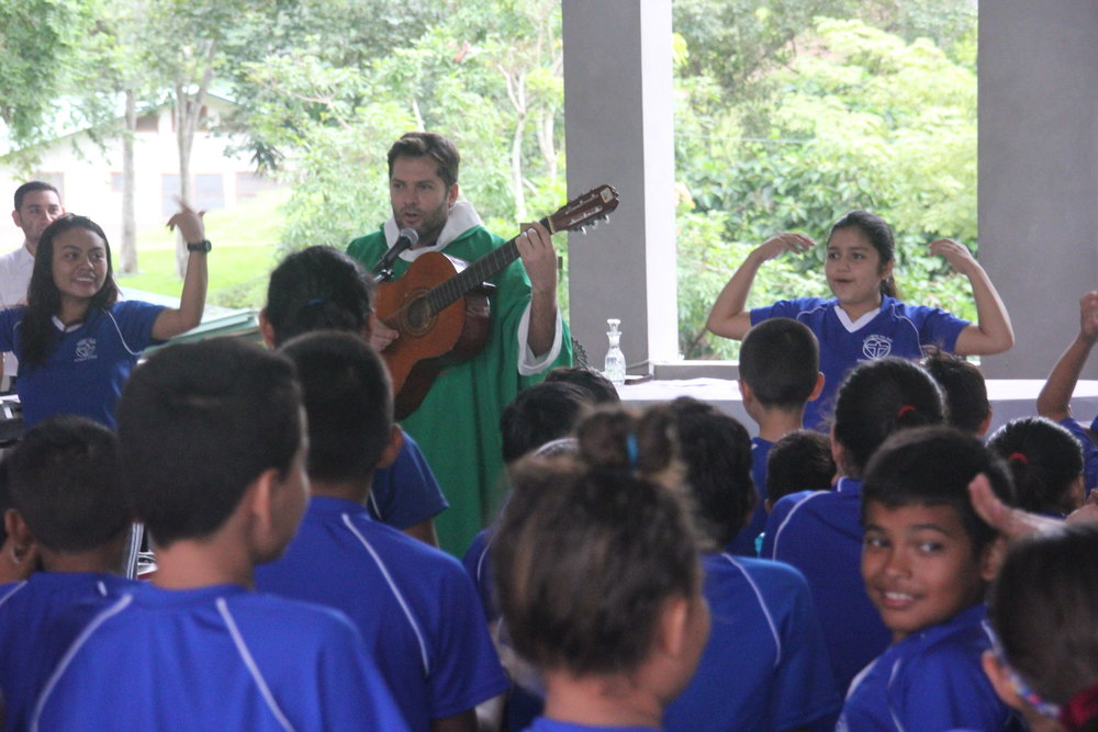 Padre 'Pato' singing with the children of Amigos on the First Day of School, August 2018.