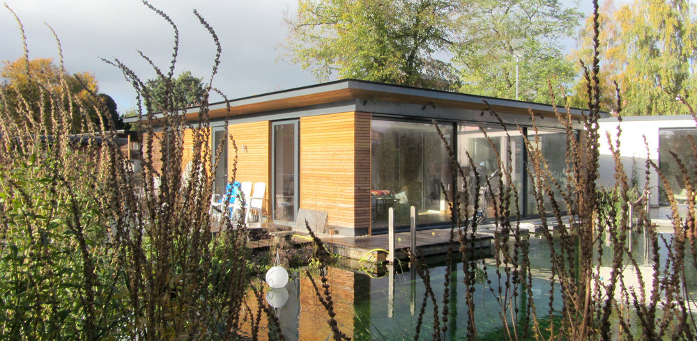 Bedroom block with larch cladding as viewed from across the natural swimming pond