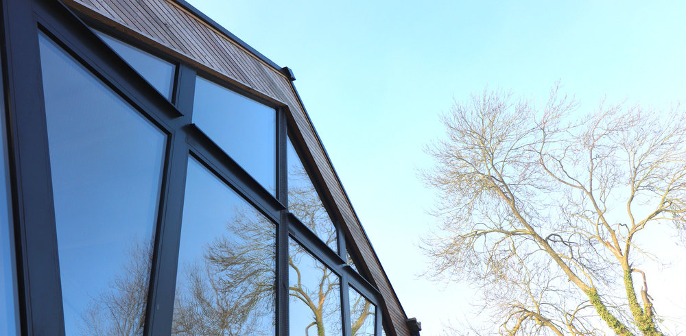 reflection in glass of gable end to barn conversion