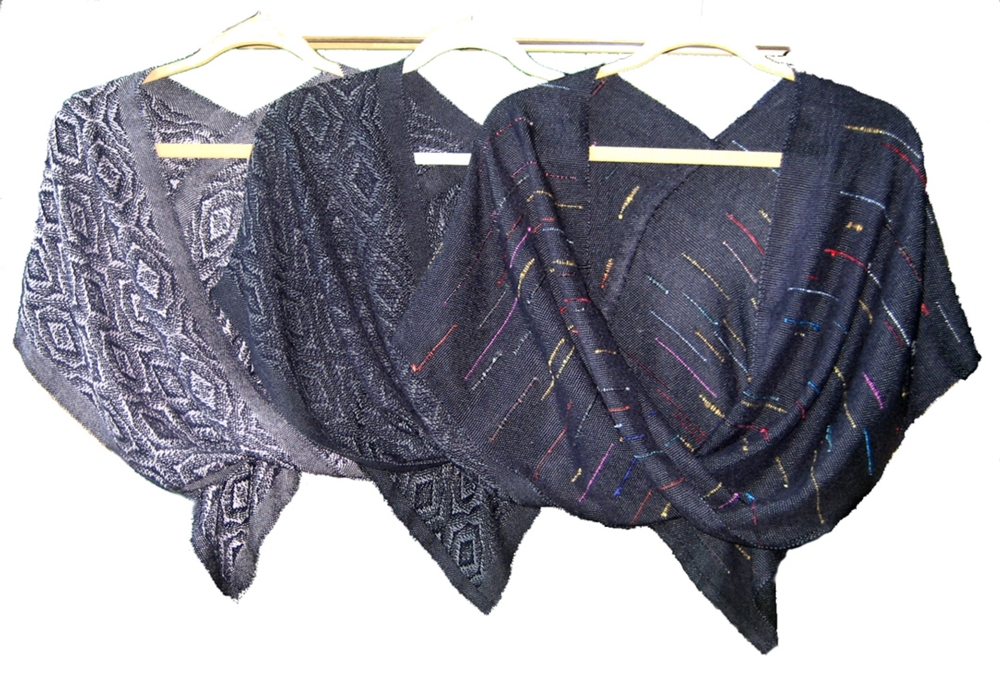 The warp thread in each of these three shawls is midnight blue bamboo. Its silky sheen gives them a luxurious sheen, weight and feel. Bamboo, like silk, is warm in the cooler temperatures and cool in the summer heat. Just the right pick for a breezy summer night or a cool Fall day. The shawl on the far left is woven in a twill pattern of lilac bamboo. The shawl in the center is woven with a silver gray bamboo. The shawl to the left is woven with midnight blue bamboo sprinkled in silk and handspun thrums (pieces of prior warps).