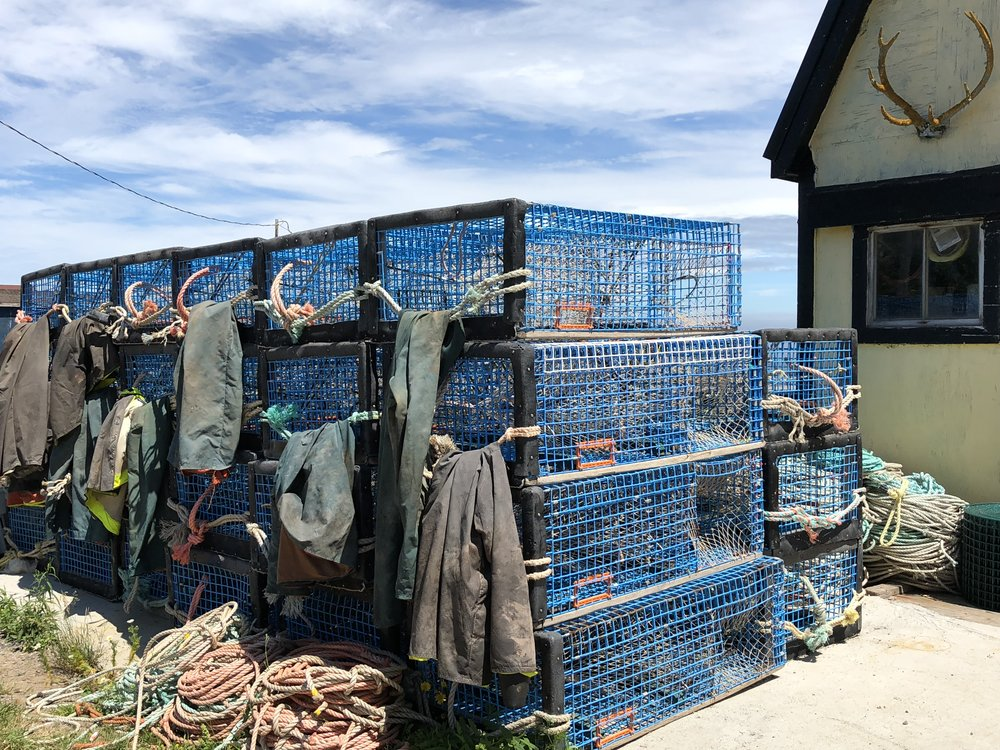 Foul weather gear drying on blue lobster pots.