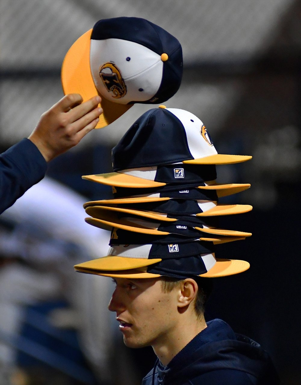 Players place their hats in a stack on top of Chris Martin's head making their own unique version of a rallycap, or good luck charmto get a win, during a lull in Kent's game against Toldeo University Friday April 21, 2017.
