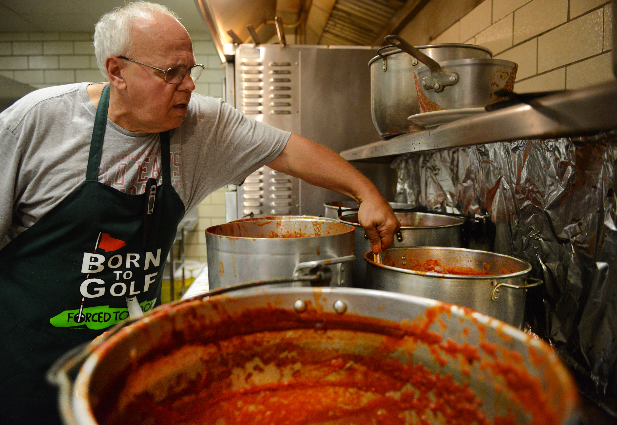 Lou Lazzaro stirs tomato sauce for Italian meals for Festa Italiana at Mount Saint Peter Parish in New Kensington on Thursday, July 30, 2015.