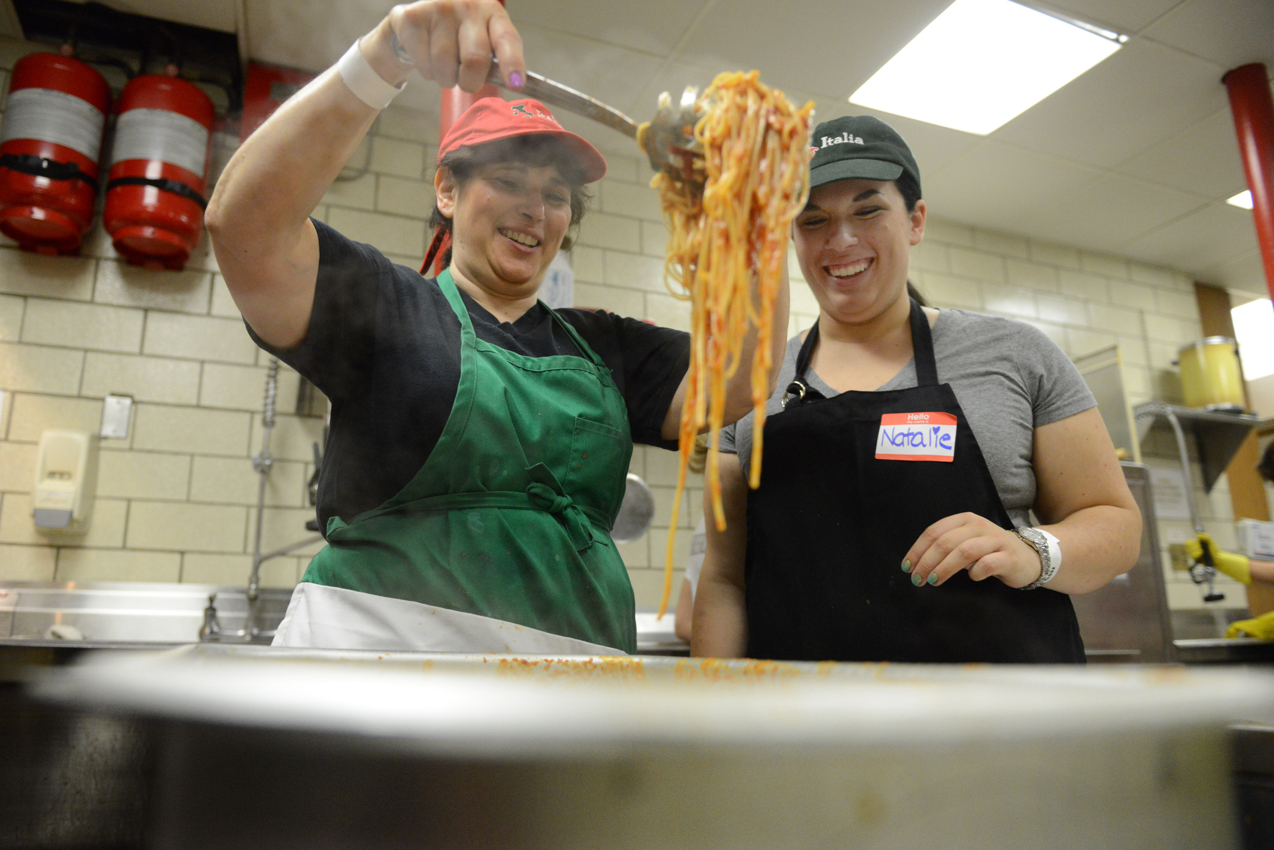 Nancy Brock laughs with her daughter Natalie Brock (right) as they dish out spaghetti to be served at Festa Italiana at Mount Saint Peter Parish in New Kensington on Thursday, July 30, 2015.