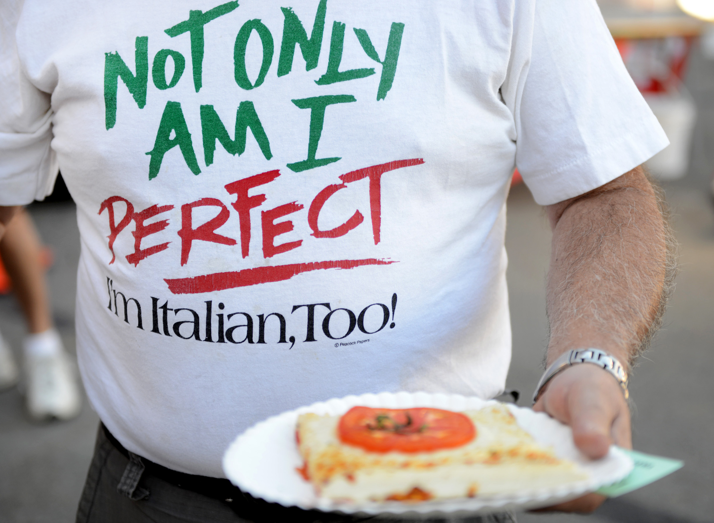 Jim Tallarico, of Lower Burrell, shows off a slice of pizza and a festive shirt at Festa Italiana at Mount Saint Peter Parish in New Kensington on Thursday, July 30, 2015.