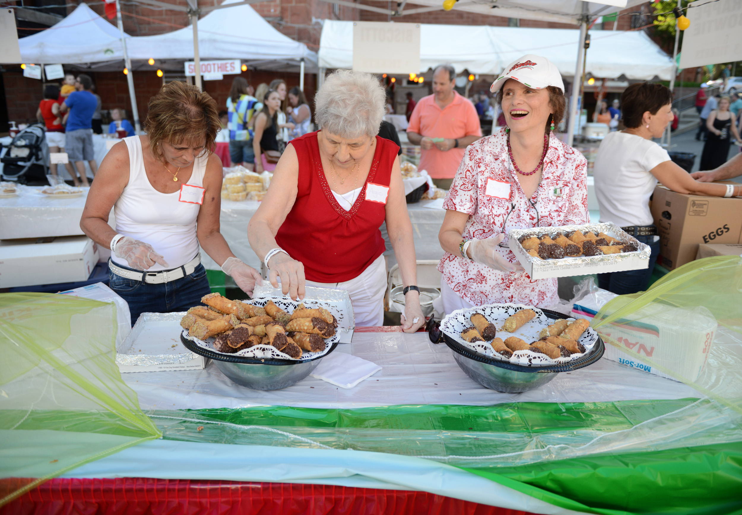 (from left) Sue Landis, of New Kensington, Angie Martino, of West Deer Township, and Paula Silowash, of Penn Township but formerly of New Kensington, work together to display cannoli at the Festa Italiana at Mount Saint Peter Parish in New Kensington on Thursday, July 30, 2015.