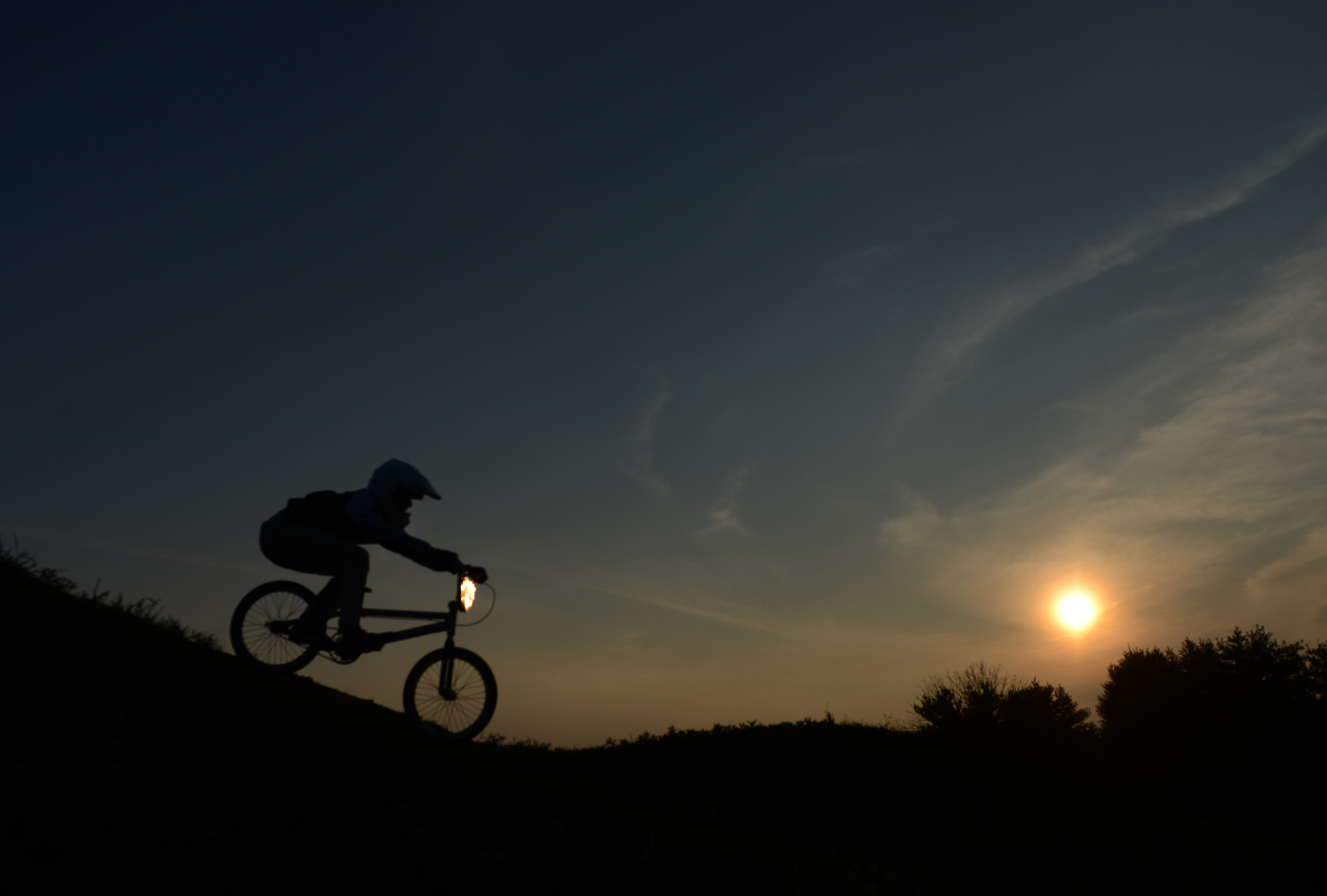 Ean Slater is silhouetted as he leads his moto at the BMX track in Northmoreland Park in Allegheny Township on Tuesday, July 28, 2015.