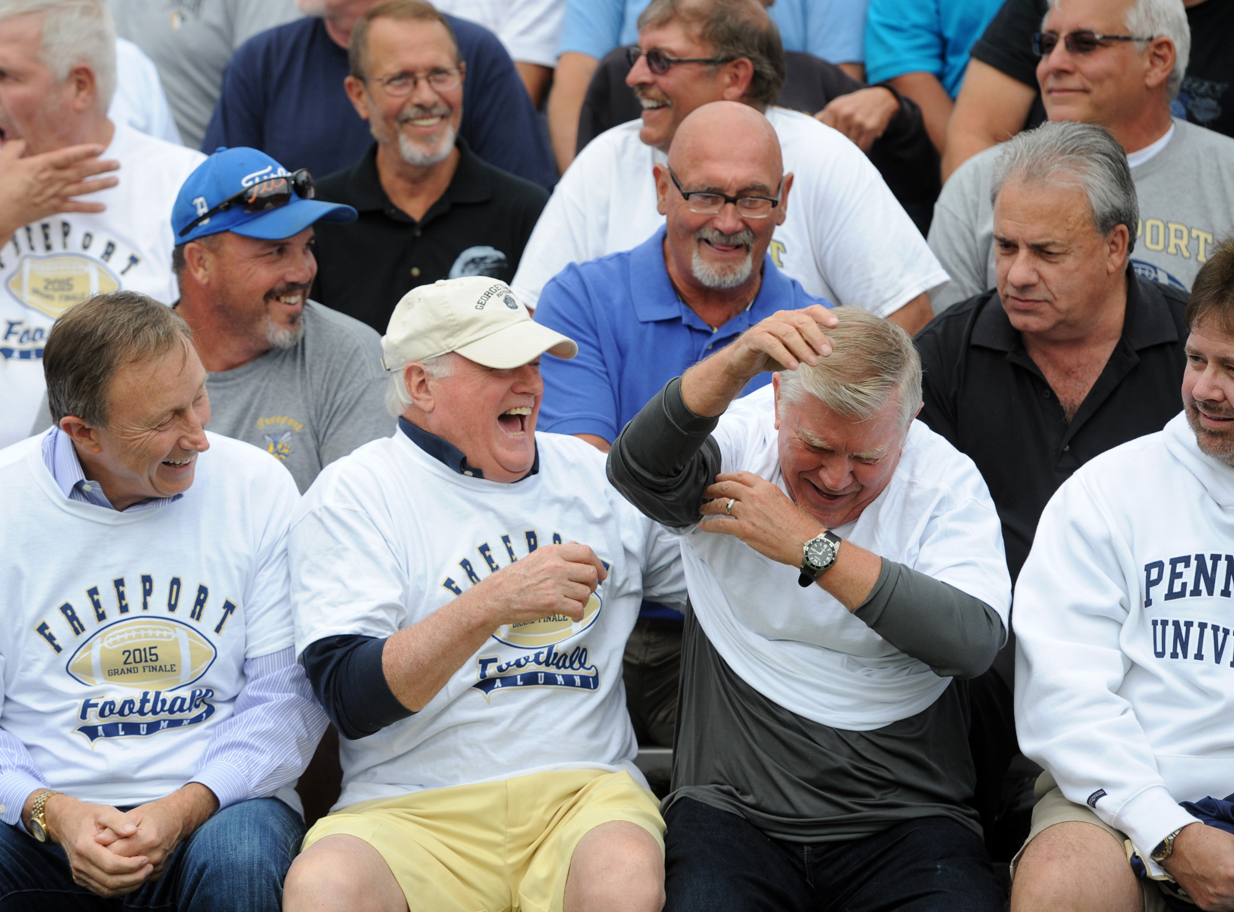 Freeport High School 1964 graduate Chip Young laughs after pointing out that his cousin, 1959 graduate Tom Fair, of Buffalo Township, put his shirt on backwards while waiting for a posed photo of Freeport High School alumnus at James Swartz Stadium in Freeport on Wednesday, Aug. 26, 2015. This will be the final season of football to be played at the stadium.