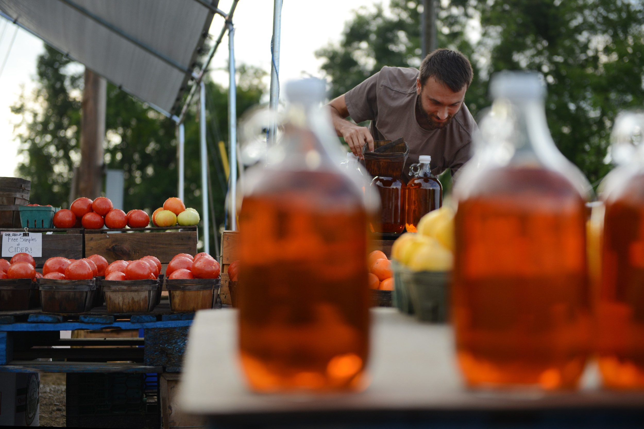 Jaymes Peluso-Hoffman, of Bloomfield, is framed between jugs of cider as he arranges tomatoes at the Golden Apple produce stand in Buffalo Township on Tuesday, Aug. 18, 2015. The produce stand will be open through the fall season.